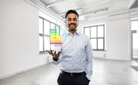 business, efficiency and saving concept - smiling indian businessman or realtor with energy consumption level chart over empty office room background 版權商用圖片