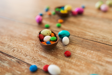 easter, sweets and confectionery concept - close up of chocolate egg and candy drops on wooden table Foto de archivo