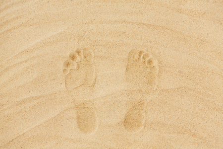 summer vacation concept - footprints in sand on beach