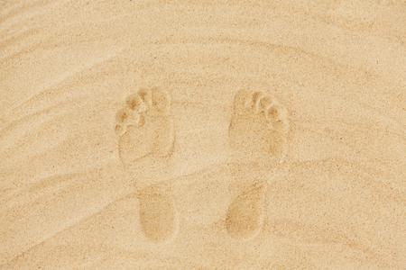 concept de vacances d'été - empreintes de pas dans le sable sur la plage