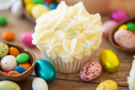 easter, food and sweets concept - frosted cupcakes with chocolate eggs and candies on table