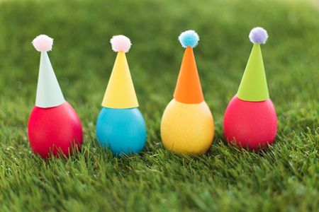easter, holidays, tradition and object concept - row of colored eggs in party hats on artificial grass