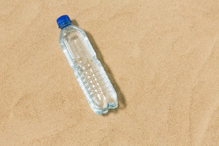 hydration and summer concept - bottle of water on beach sand