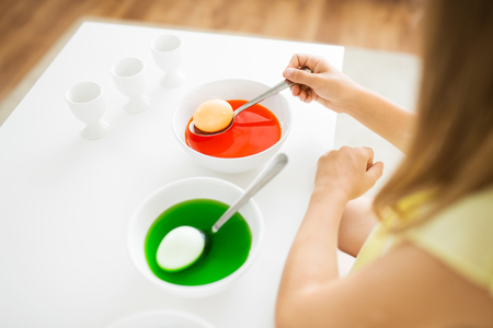 easter, holidays and people concept - close up of girl coloring eggs by red and green liquid dyes at home