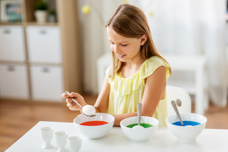 easter, holidays and people concept - happy girl coloring eggs by liquid dye at home