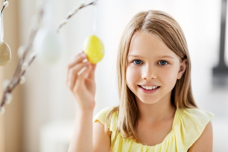 easter, holidays and people concept - happy girl decorating willow branches by toy eggs at home