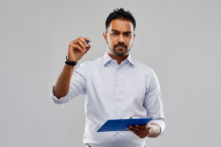 strained indian businessman writing to clipboard