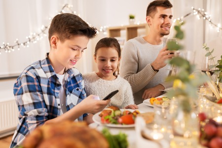 children with smartphone at family dinner party