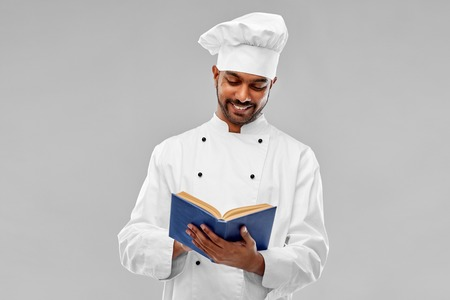 happy male indian chef reading cookbook