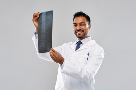 smiling indian doctor looking at spine x-ray
