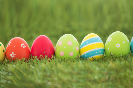 row of colored easter eggs on artificial grass Stock Photo