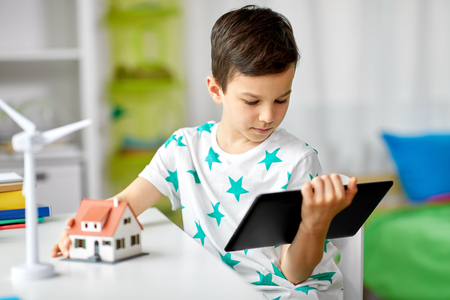boy with tablet, toy house and wind turbine Фото со стока - 116494393