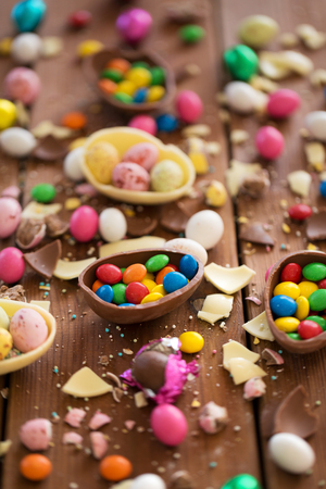 chocolate eggs and candy drops on wooden table Foto de archivo