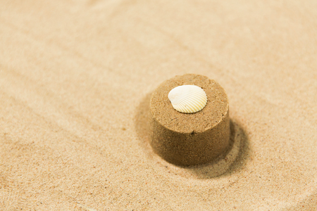 sand shape made by mold with shell on summer beach
