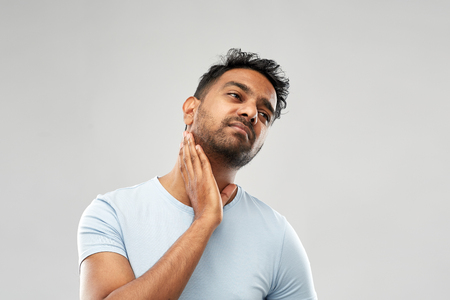 indian man suffering from sore glands or tonsils