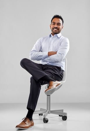 smiling indian businessman sitting on office chair Stock Photo