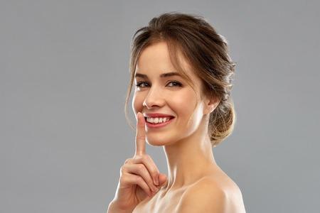 beautiful smiling woman making hush gesture Stock Photo