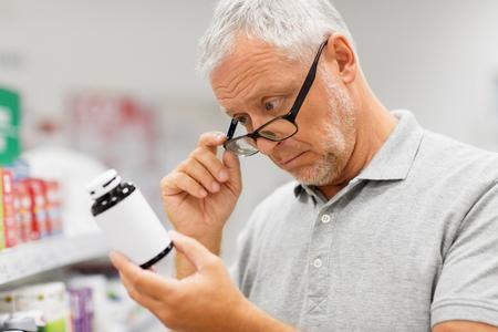 älterer männlicher Kunde mit Medikament in der Apotheke