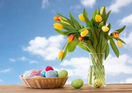 colored easter eggs in basket and flowers Foto de archivo - 117705231