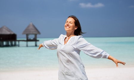 happy woman over beach and bungalow on background