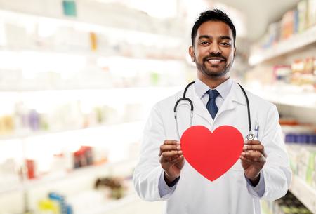 medico maschio indiano sorridente con forma di cuore rosso Archivio Fotografico