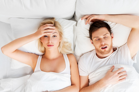 unhappy woman in bed with snoring sleeping man
