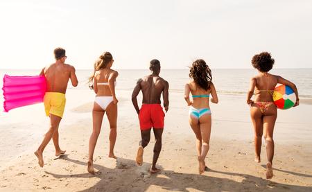 friends run with beach ball and swimming mattress 版權商用圖片 - 116793724