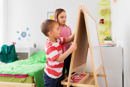 happy kids drawing on easel or flip board at home