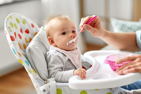 father feeding baby sitting in highchair at home