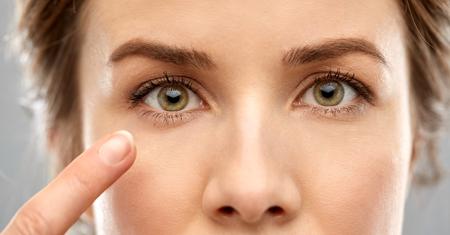 close-up van een vrouw die met de vinger naar het oog wijst