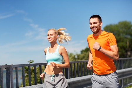 couple with fitness trackers running along bridge