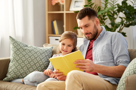 happy father and daughter reading book at home Imagens