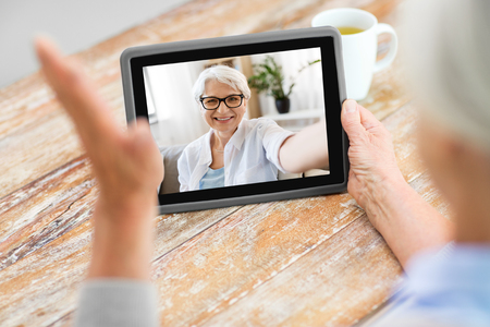 technology, communication and people concept - happy senior woman having video call with old friend on tablet computer at home