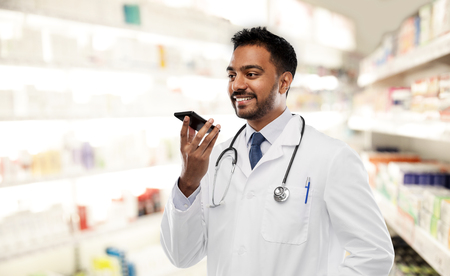 medicine, technology and healthcare concept - smiling indian male doctor or pharmacist in white coat with stethoscope using voice command recorder over drugstore background