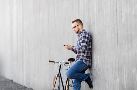 technology, leisure and lifestyle- happy young hipster man in earphones with smartphone and fixed gear bike listening to music on city street