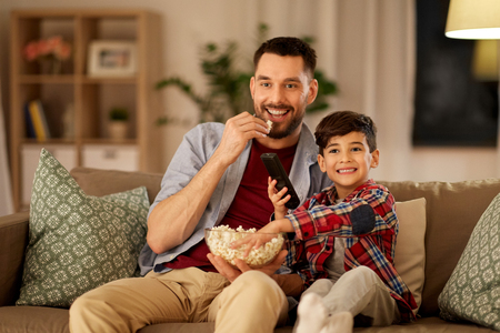 happy father and son watching tv at home Stock Photo