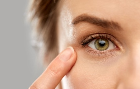 close up of woman pointin finger to eye Stock Photo