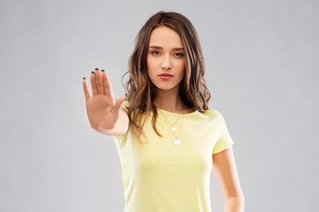 young woman or teenage girl showing stop gesture