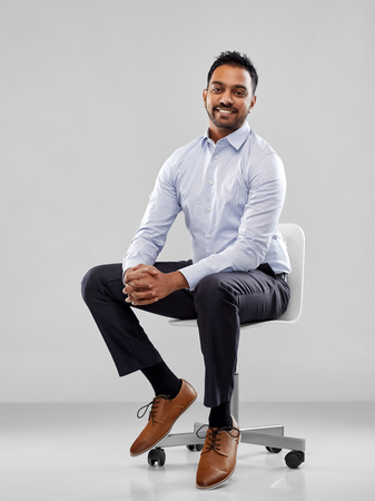 smiling indian businessman sitting on office chair 版權商用圖片