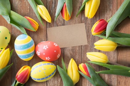 easter, holidays, tradition and object concept - close up of colored eggs and tulip flowers over wooden boards background