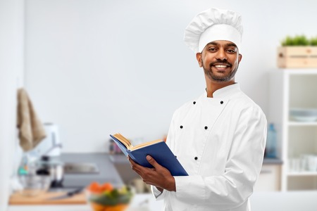 cooking, profession and people concept - happy male indian chef in toque with cookbook over kitchen background