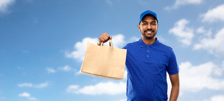service and people concept - happy indian delivery man food in paper bag in blue uniform over sky and clouds background