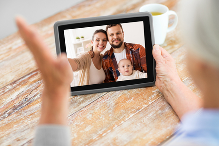 technology, communication and people concept - senior woman having video call with happy family on tablet computer at home