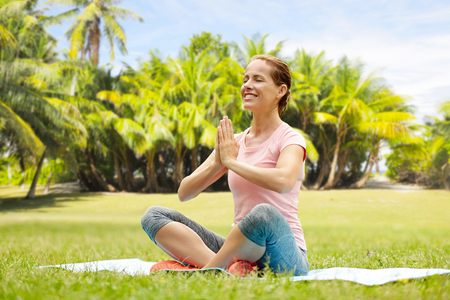 fitness, yoga and healthy lifestyle concept - happy woman meditating in exotic summer park over french polynesia background