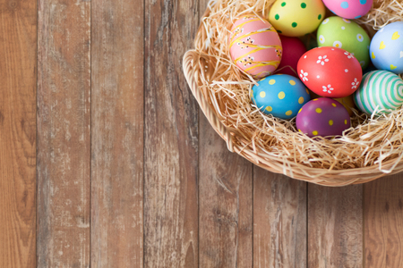 easter, holidays, tradition and object concept - close up of colored eggs in wicker basket over wooden boards background