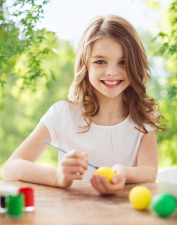 easter, holidays and people concept - happy smiling girl coloring eggs over green natural background Imagens