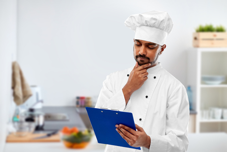 cooking, profession and people concept - male indian chef in toque reading menu on clipboard over kitchen background Foto de archivo