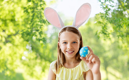 easter, holidays and people concept - happy girl wearing bunny ears headband with colored egg over green natural background