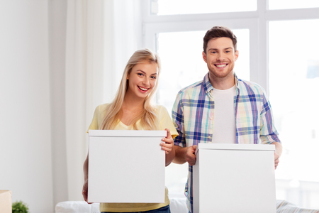 mortgage, people and real estate concept - happy couple with boxes moving to new home