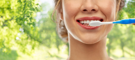 oral care, dental hygiene and people concept - close up of smiling woman with toothbrush cleaning teeth over green natural background Stock Photo